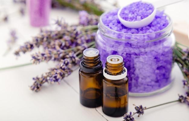 Huiles essentielles de lavande et sel marin de violette, fleurs de lavande. produits de bain à la lavande traitement d'aromathérapie sur fond de bois blanc. les produits cosmétiques de bain de beauté spa de soins de la peau détendent l'aromathérapie.