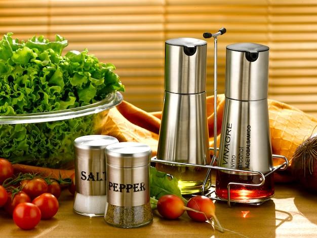 Huilier et vinaigre ensemble et bocaux salière et poivrière sur une table de cuisine