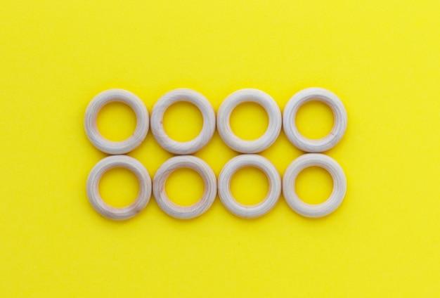 Huit anneaux en bois sur fond jaune. anneau de dentition pour bébé en bois naturel. jouet pour enfants respectueux de l'environnement. vue de dessus, mise à plat avec espace de copie.
