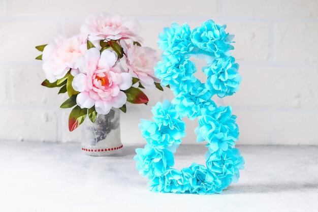Huit bricolage en carton artificiel décoré de fleurs artificielles fait de papier de soie bleu à fond blanc.