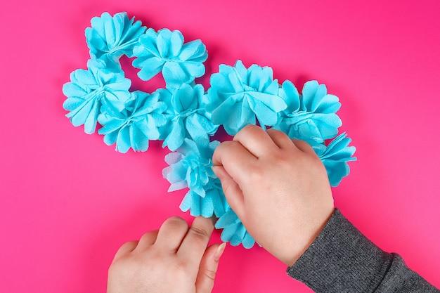 Huit bricolage en carton décoré de fleurs artificielles en papier de soie bleu fond rose.