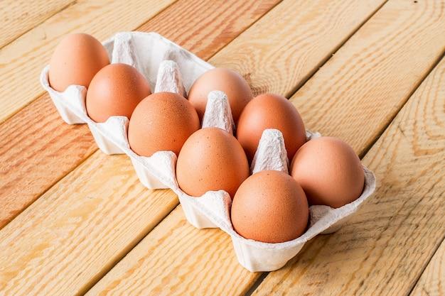 Huit œufs en boîte sur une table en bois