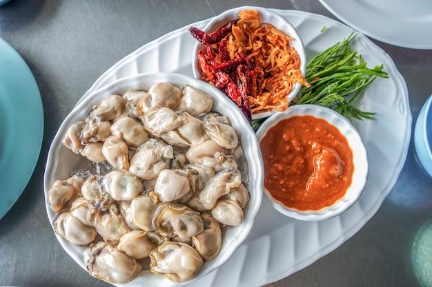 Huître sur glace avec sauce épicée frite et oignon
