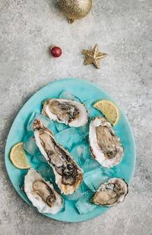 Huîtres au citron, glace et vin blanc sur fond de béton avec un décor festif. dîner de noël