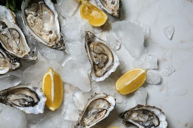 Huîtres crues savoureuses avec de la glace et du citron sur table lumineuse