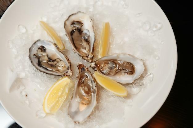 Huîtres fraîchement ouvertes sur une assiette avec de la glace, des tranches de citron, des brins de menthe et de romarin sur un espace en pierre sombre. place pour le texte, vue de dessus. dîner romantique dans un restaurant.
