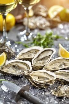 Huîtres fraîches ouvertes sur glace avec citron et vin blanc