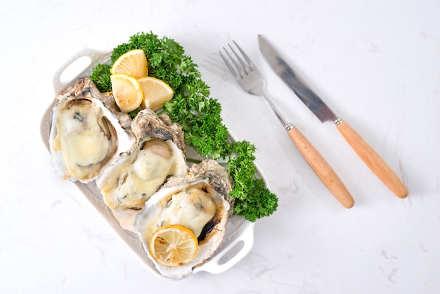 Huîtres fraîches ouvertes sur une plaque blanche. mise au point sélective