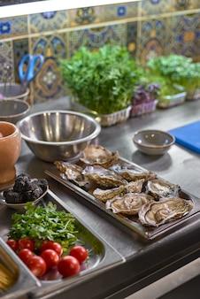 Huîtres et ingrédients au plat sur la table dans la cuisine.
