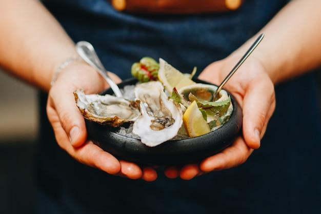 Huîtres magnifiques sur une assiette sombre dans les mains des hommes