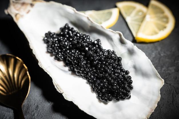 Huîtres ouvertes avec caviar d'esturgeon noir et citron sur glace sur table en béton noir. vue de dessus, mise à plat, espace de copie.