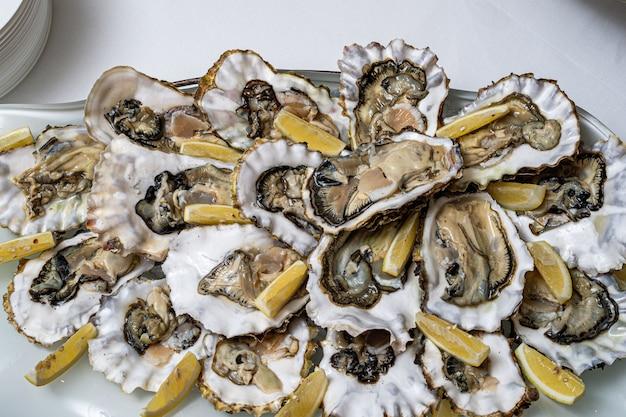 Huîtres ouvertes fraîches sur une plaque blanche. dans l'apéritif du restaurant