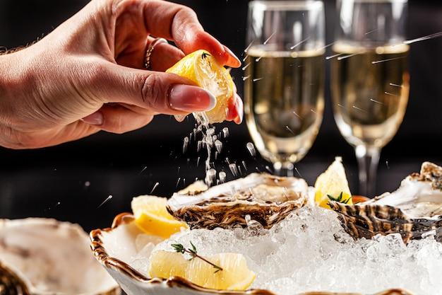 Les huîtres ouvertes se trouvent sur de la glace pilée avec du citron