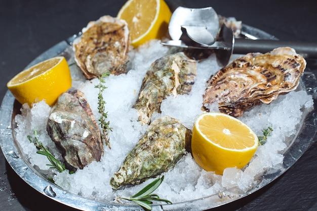 Huîtres sur plaque de pierre avec glace et citron.