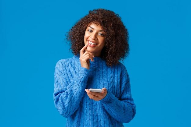 Hum ... intéressant. intrigué et rêveur, créatif fille afro-américaine pense-up message de félicitation de noël, tenant le smartphone souriant et touchant la lèvre réfléchie