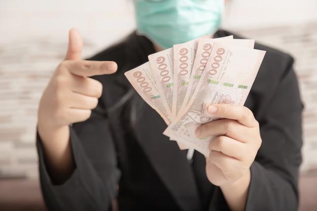 Un humain portant un masque médical et un costume noir pointant l'argent dans sa main.