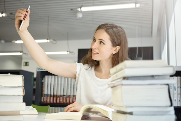 Humain et technologie. les gens et l'éducation. portrait intérieur d'une adolescente de race blanche à la bibliothèque essayant de prendre un selfie, entouré de livres et de manuels