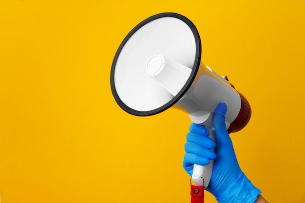 Human hand holding haut-parleur électronique contre jaune