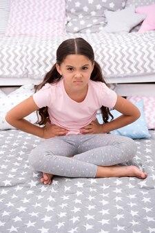 Humeur capricieuse. petite fille assise dans la chambre. kid malheureux capricieux quelqu'un est entré dans sa chambre dérangeant. fille enfant cheveux longs pyjama mignon visage capricieux. laissez-la se calmer. comment apprivoiser enfant capricieux.