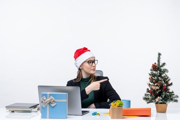 L'humeur du nouvel an avec une femme blonde avec un chapeau de père noël assis à une table avec un arbre de noël et un cadeau dessus pointant quelque chose sur la gauche sur fond blanc