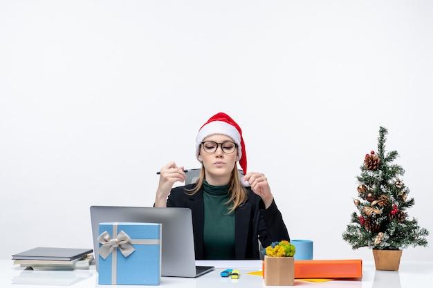L'humeur du nouvel an avec femme blonde décisive avec un chapeau de père noël assis à une table avec un arbre de noël et un cadeau sur elle sur fond blanc