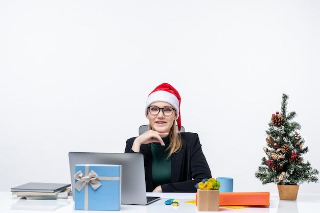 L'humeur du nouvel an avec une femme séduisante souriante avec un chapeau de père noël assis à une table avec un arbre de noël et un cadeau dessus dans le bureau