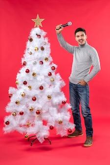 L'humeur du nouvel an avec un gars positif habillé en jeans debout près de l'arbre de noël décoré et s'amuser sur le rouge