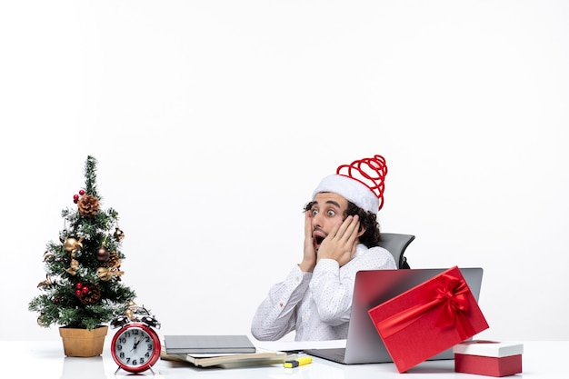 L'humeur du nouvel an avec un jeune homme d'affaires excité choqué avec un chapeau de père noël assis au bureau sur fond blanc