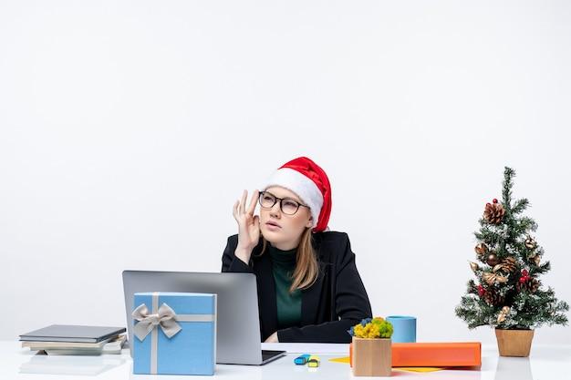 L'humeur du nouvel an avec jolie femme confuse avec un chapeau de père noël assis à une table avec un arbre de noël et un cadeau dessus dans le bureau