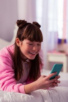 Humeur joyeuse. adolescent ravi positif gardant le sourire sur son visage tout en regardant son gadget