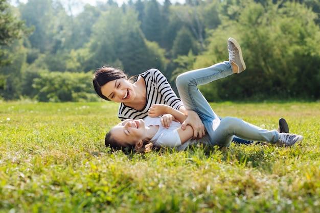 Humeur joyeuse. heureuse femme charmante gaffant avec sa petite fille en position couchée sur l'herbe dans la prairie du parc ensoleillée