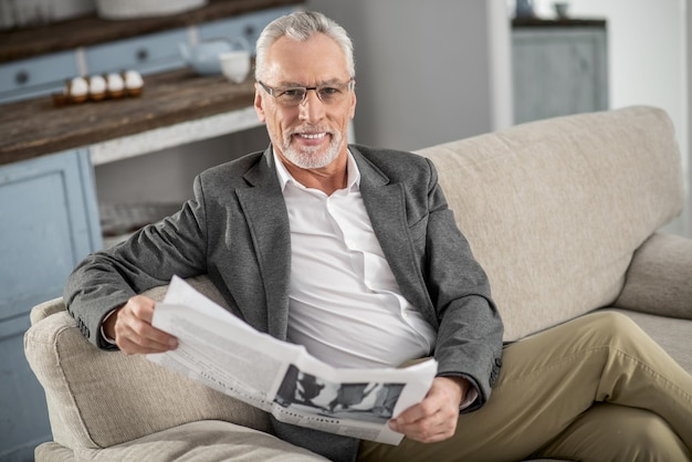 Humeur joyeuse. homme ravi positif croisant les jambes alors qu'il était assis sur son canapé et souriant à la caméra