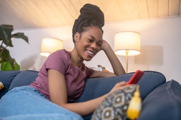 Humeur joyeuse. joyeuse jeune femme à la peau foncée avec une coiffure et un sourire à pleines dents avec un smartphone assis sur un canapé dans une chambre moderne et confortable