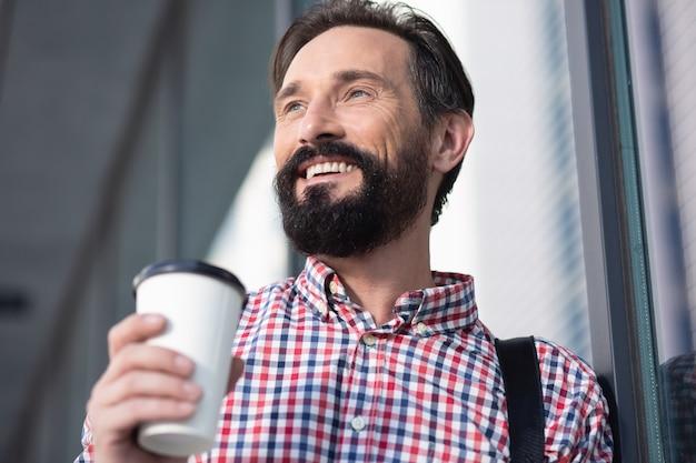 Humeur matinale. gros plan d'un homme barbu joyeux, boire du café tout en regardant de côté