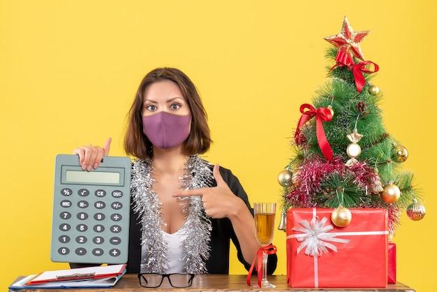 L'humeur de noël avec une belle dame concentrée en costume portant un masque médical pointant la calculatrice dans le bureau sur jaune