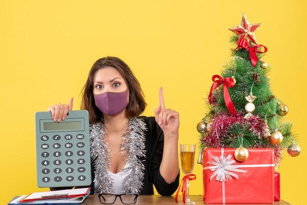 L'humeur de noël avec une belle dame concentrée en costume portant un masque médical tenant une calculatrice au bureau sur jaune