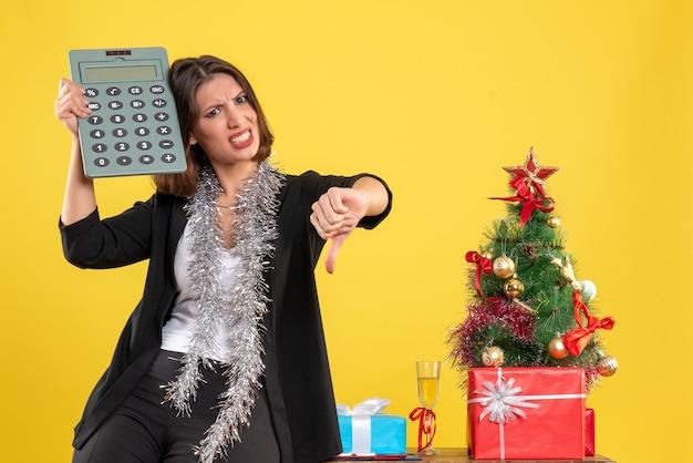 L'humeur de noël avec une belle dame nerveuse debout dans le bureau et tenant la calculatrice faisant un geste négatif au bureau sur jaune