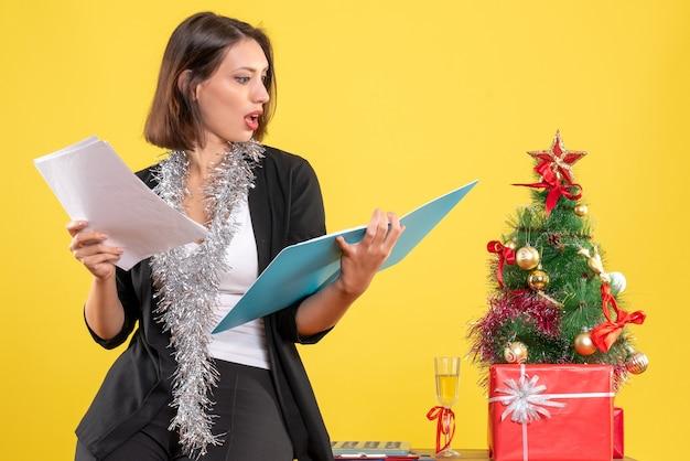 Humeur de noël avec une belle dame souriante debout dans le bureau et enquêtant sur des documents