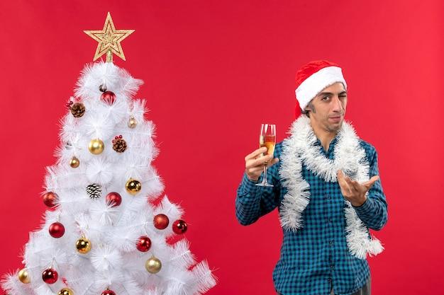 L'humeur de noël avec curieux jeune homme avec chapeau de père noël dans une chemise rayée bleu soulevant un verre de vin près de l'arbre de noël