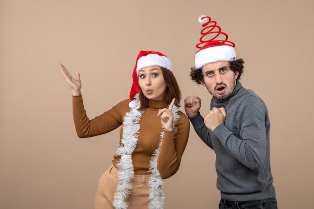 L'humeur de noël avec excité cool satisfait surpris charmant couple portant des chapeaux de père noël rouge pointant au-dessus