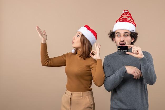 L'humeur de noël avec excité heureux surpris cool couple portant des chapeaux de père noël rouge montrant la carte bancaire