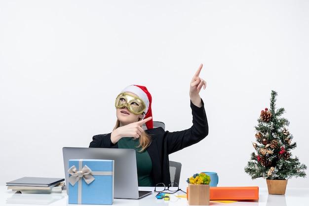 L'humeur de noël avec excité positive jeune femme avec chapeau de père noël et portant un masque assis à une table pointant ci-dessus sur le côté gauche sur fond blanc