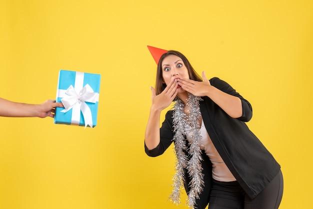 L'humeur de noël avec une femme d'affaires excitée en costume avec un chapeau de noël et une main tenant un cadeau sur le jaune