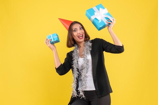 L'humeur de noël avec une femme d'affaires excitée en costume avec un chapeau de noël montrant son cadeau sur jaune