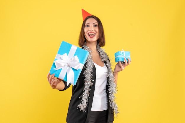 L'humeur de noël avec une femme d'affaires fière en costume avec chapeau de noël montrant son cadeau sur jaune