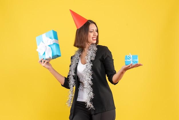 L'humeur de noël avec une femme d'affaires positive en costume avec un chapeau de noël en regardant ses cadeaux sur jaune