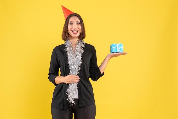 Humeur de noël avec une femme d'affaires positive en costume avec un chapeau de noël et tenant un cadeau sur jaune