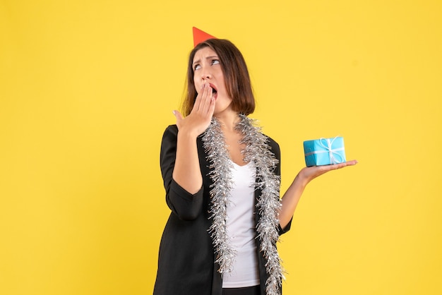 L'humeur de noël avec une femme d'affaires surprise choquée en costume avec chapeau de noël et tenant un cadeau sur jaune