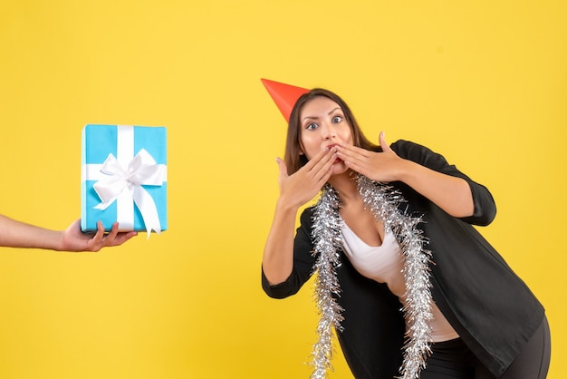 L'humeur de noël avec une femme d'affaires surprise en costume avec un chapeau de noël et une main tenant un cadeau sur le jaune