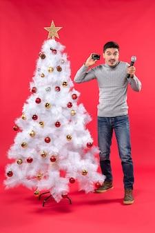L'humeur de noël avec un gars confiant habillé en jeans debout près de l'arbre de noël décoré et tenant un microphone et son téléphone